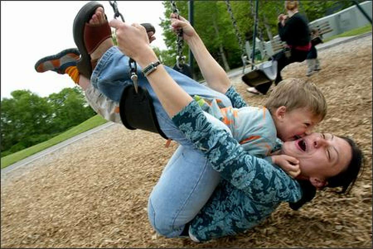 Vera Ranguelova and son Yoan, 3, of Lake City take advantage of some nice weather earlier this week to try out a swing set in Laurelhurst. They had mixed success.