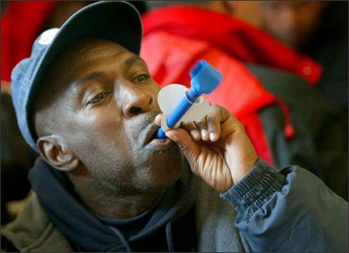 Eddie Samuels blows a party horn during a service Thursday at the Union Gospel Mission honoring the birthdays of Seattle homeless people. It was the second year that the mission has honored the birthdays of the homeless, regardless of their actual birth dates.