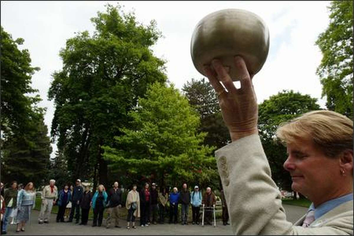 Richard Levy, senior minister of Seattle Unity Church, raises a Tibetan bowl that he rang to start the group's part of a global five minutes of silence at Denny Park on Sunday.