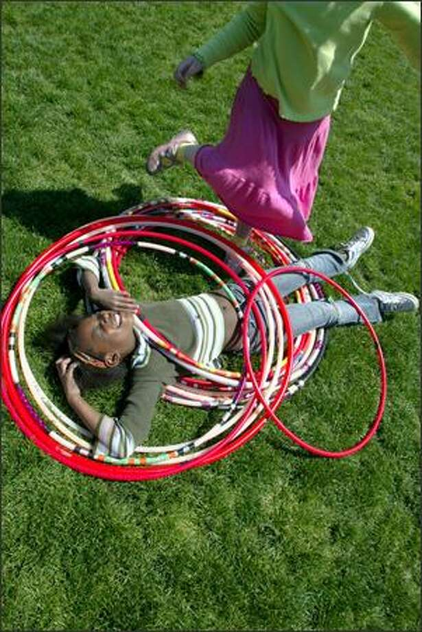 Nkechi Ogugua takes a break among the hula hoops as her friend Isabella Geist plays with them during the Seattle International Children's Festival at the Seattle Center. Both 8-year-olds are students at Daniel Bagley Elementary School. The festival runs through Saturday. For information: www.seattleinternational.org Photo: Karen Ducey, Seattle Post-Intelligencer / Seattle Post-Intelligencer