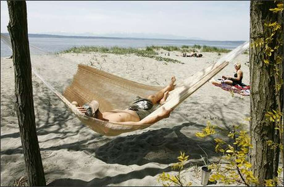 Dean Chi enjoys the sun and a swing on a hammock while relaxing with his girlfriend, Jessica Lechsinger, at Golden Gardens Beach on Tuesday. Photo: Gilbert W. Arias, Seattle Post-Intelligencer / Seattle Post-Intelligencer