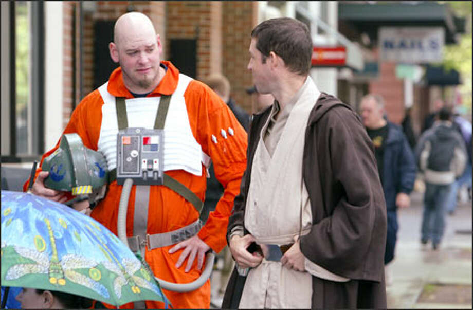 """Star Wars"" fans Jason Burrows, left, dressed as an X-wing pilot, and Jedi Knight Greg Evans line up on Fifth Avenue in Seattle in anticipation of the midnight showing of ""Star Wars: Episode III -- Revenge of the Sith."" Photo: Gilbert W. Arias, Seattle Post-Intelligencer / SEATTLE POST- INTELLIGENCER"