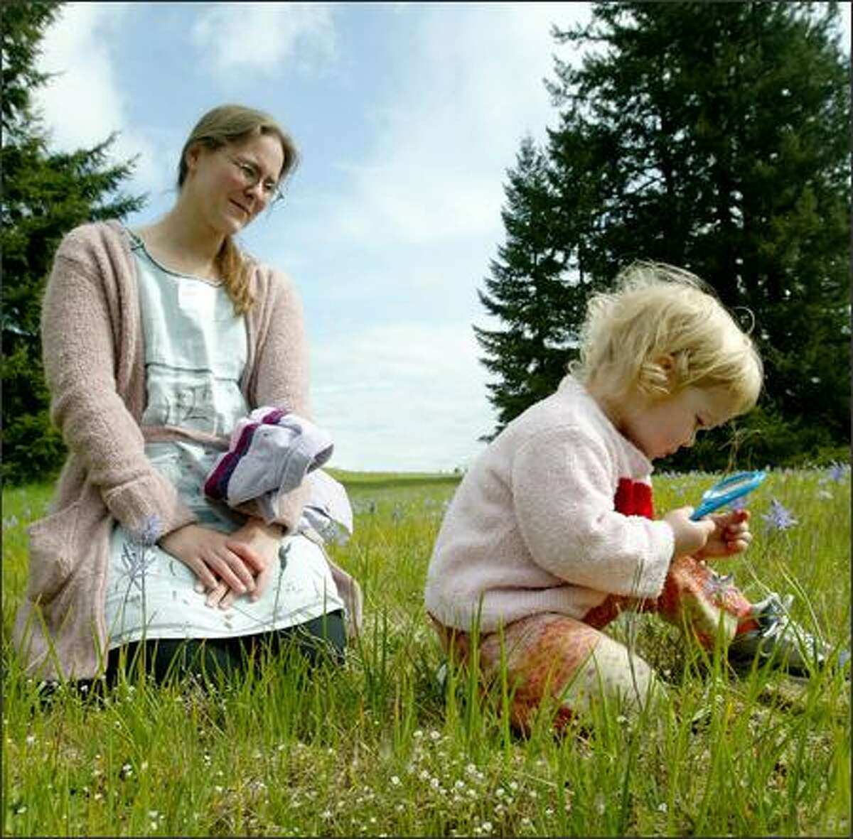 Two-year-old Thea Byrne looks at a camas through a magnifying glass at the Glacial Heritage Preserve near Littlerock as mom Gabby looks on.