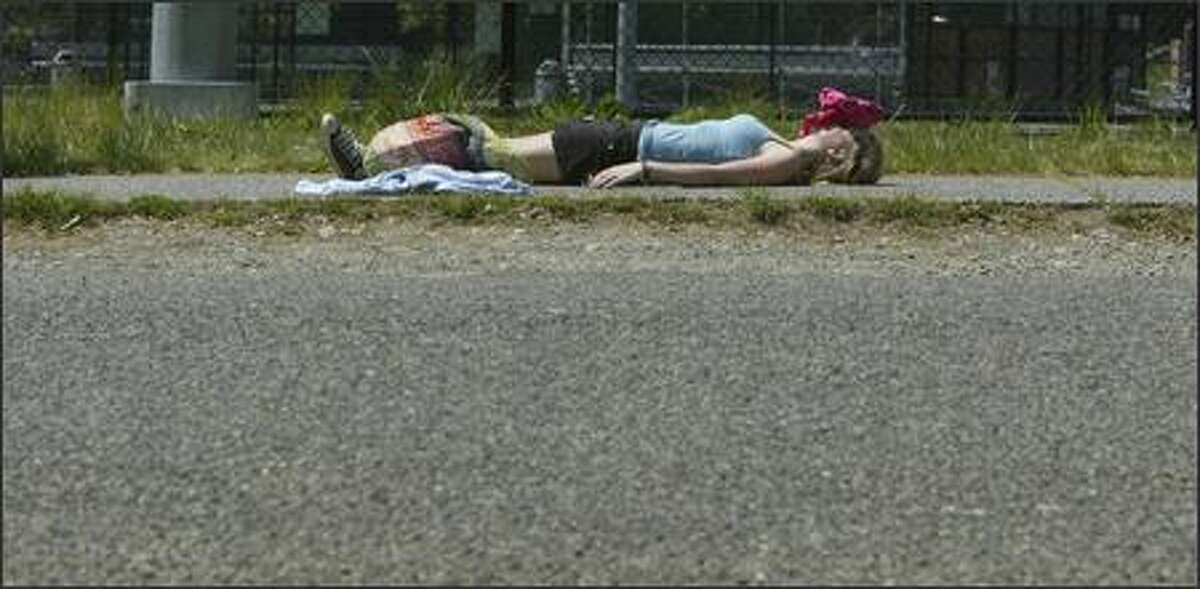 Nathan Hale High School freshman Julie Prskalo, 15, catches some rays in Tuesday's record heat while waiting for a friend to meet her near the school. When faced with whether to use her shirt as a pillow or a shield from the sun, she decided she'd rather not end up with a red face.