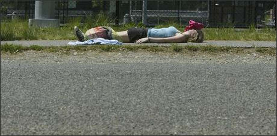 Nathan Hale High School freshman Julie Prskalo, 15, catches some rays in Tuesday's record heat while waiting for a friend to meet her near the school.  When faced with whether to use her shirt as a pillow or a shield from the sun, she decided she'd rather not end up with a red face. Photo: Andy Rogers, Seattle Post-Intelligencer / Seattle Post-Intelligencer