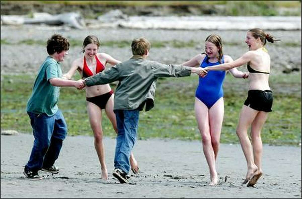 Dancing on the beach after a dip into Kilisut Harbor are twins Geneva and Hillary Pritchett with their friend Barbara Seely, 15-year-olds from Bainbridge Island.