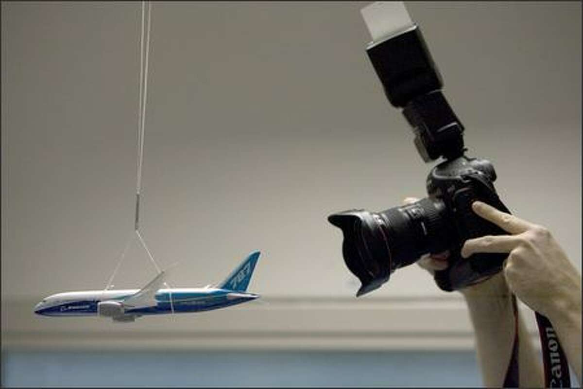 One of the dozen or so still photographers visiting Boeing's avionics integration lab photographs a model of the 787 hanging.