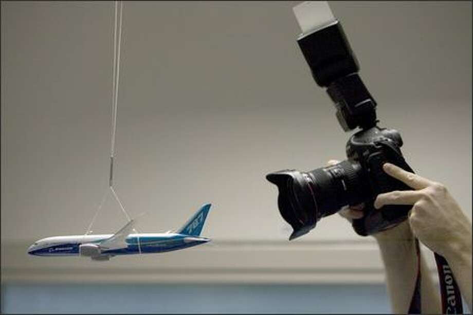 One of the dozen or so still photographers visiting Boeing's avionics integration lab photographs a model of the 787 hanging. Photo: Grant M. Haller, Seattle Post-Intelligencer / Seattle Post-Intelligencer