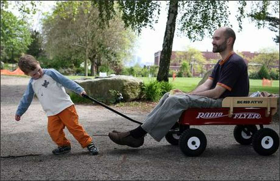 Cedar Macneale, 3, gives his dad, Neil, a turn in his wagon during an afternoon visit Wednesday to Wallingford Playfield in Seattle. Photo: Joshua Trujillo, Seattlepi.com / seattlepi.com