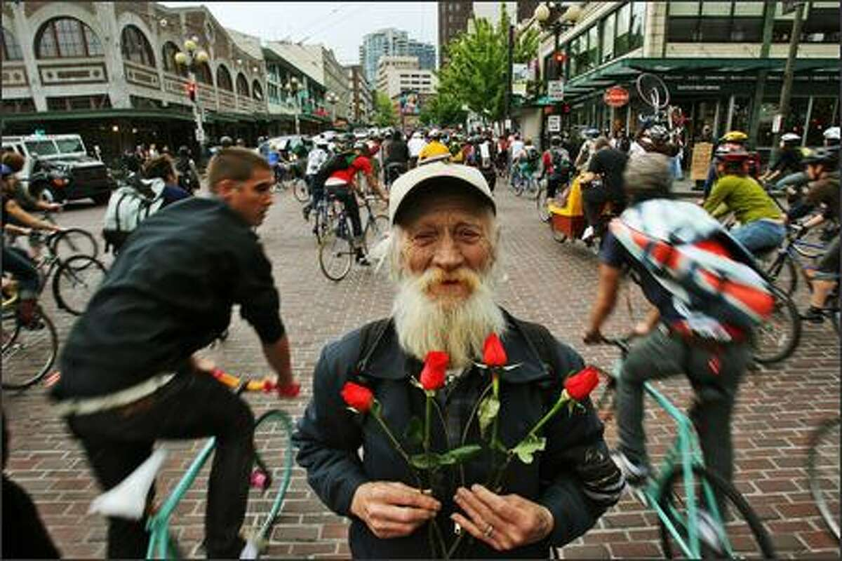 John Fisher, who was giving away roses salvaged from the flower seller's garbage cans, is caught mid-intersection by the April 26 Critical Mass bicycle rally passing the Pike Place Market.