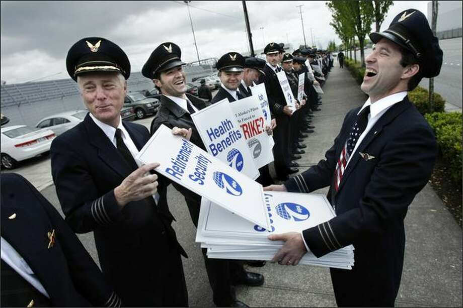 1st Officer Brian Moynihan, right, reacts as Cpt. Claude Tirman jokes about his preference for a sign addressing retirement security during an informational picket of approximately 300 Alaska Airlines pilots outside the Alaska Air Group shareholders meeting at the Museum of Flight. Photo: Andy Rogers, Seattle Post-Intelligencer / Seattle Post-Intelligencer