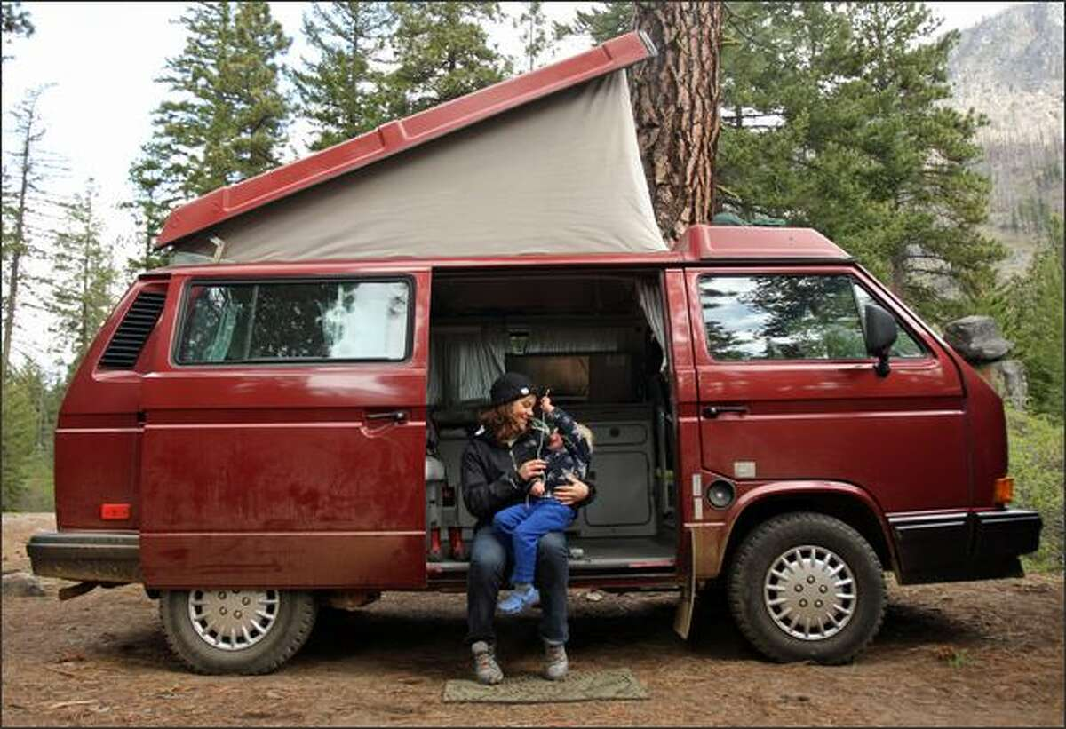 French Au Pair Camille Gaillard sits with Solomon Barnett, 2, in a friend's VW Westfalia at a campsite in Wenatchee National Forest along Icicle Creek, near Leavenworth, Wash.