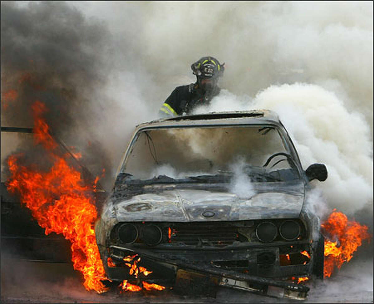 A Seattle firefighter sprays water on a car burning Wednesday along the southbound lanes of Interstate 5 just north of Mercer Street. The unoccupied car, which was burning about 4:15 p.m., briefly slowed traffic.