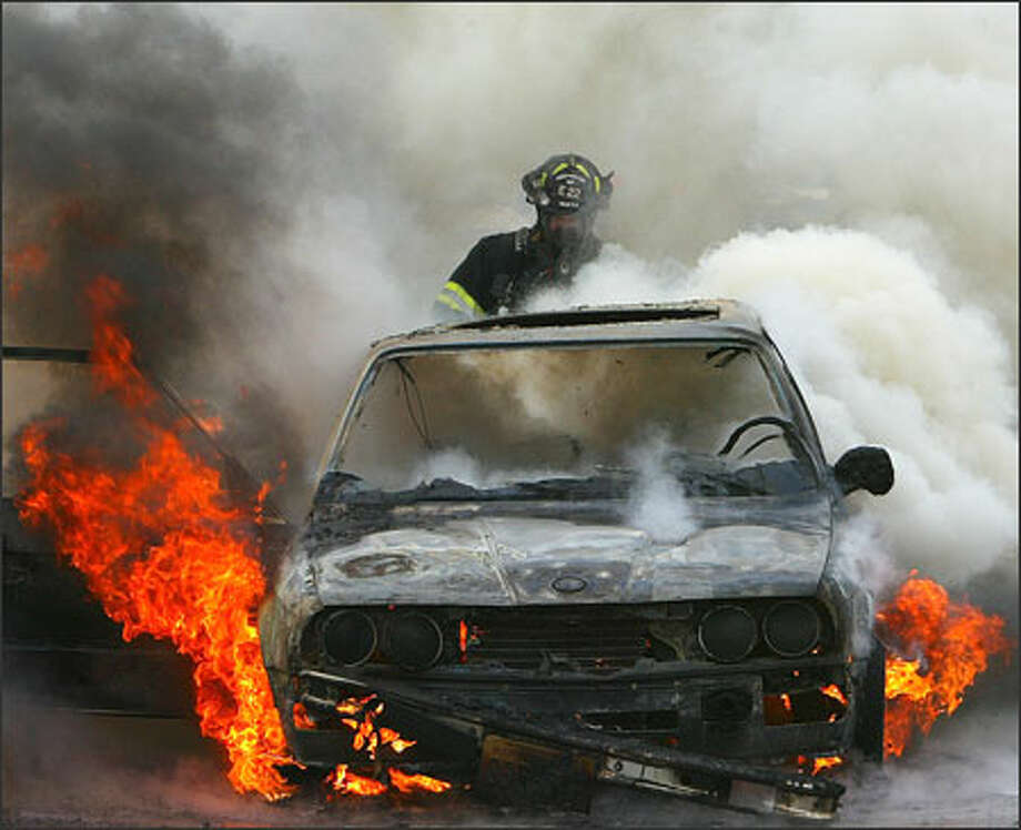 A Seattle firefighter sprays water on a car burning Wednesday along the southbound lanes of Interstate 5 just north of Mercer Street. The unoccupied car, which was burning about 4:15 p.m., briefly slowed traffic. Photo: Grant M. Haller, Seattle Post-Intelligencer / Seattle Post-Intelligencer