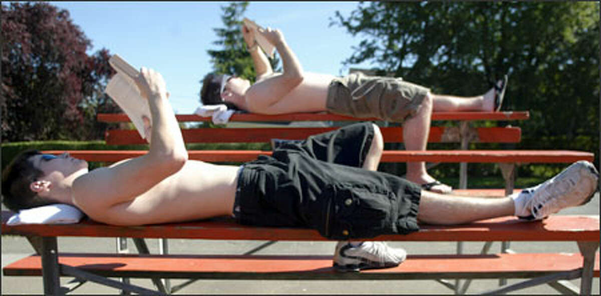 Seattle Pacific University students Chris Willson, foreground, and Jeff Lathrop catch some rays while resting on bleachers at the West Queen Anne Playfield in Seattle during a warm, sunny afternoon.