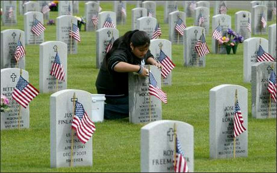 Christian Vasquez, 15, cleans a headstone Friday at Tahoma National Cemetery. Vasquez and fellow ninth-graders at Tahoma Junior High School visited the cemetery to clean headstones, raise flags and place more than 12,000 small U.S. flags at each marker as part of a history project and to help with preparations for Memorial Day weekend and a program on Monday where the featured speakers will be Gov. Christine Gregoire and Sen. Maria Cantwell. Photo: Gilbert W. Arias, Seattle Post-Intelligencer / Seattle Post-Intelligencer