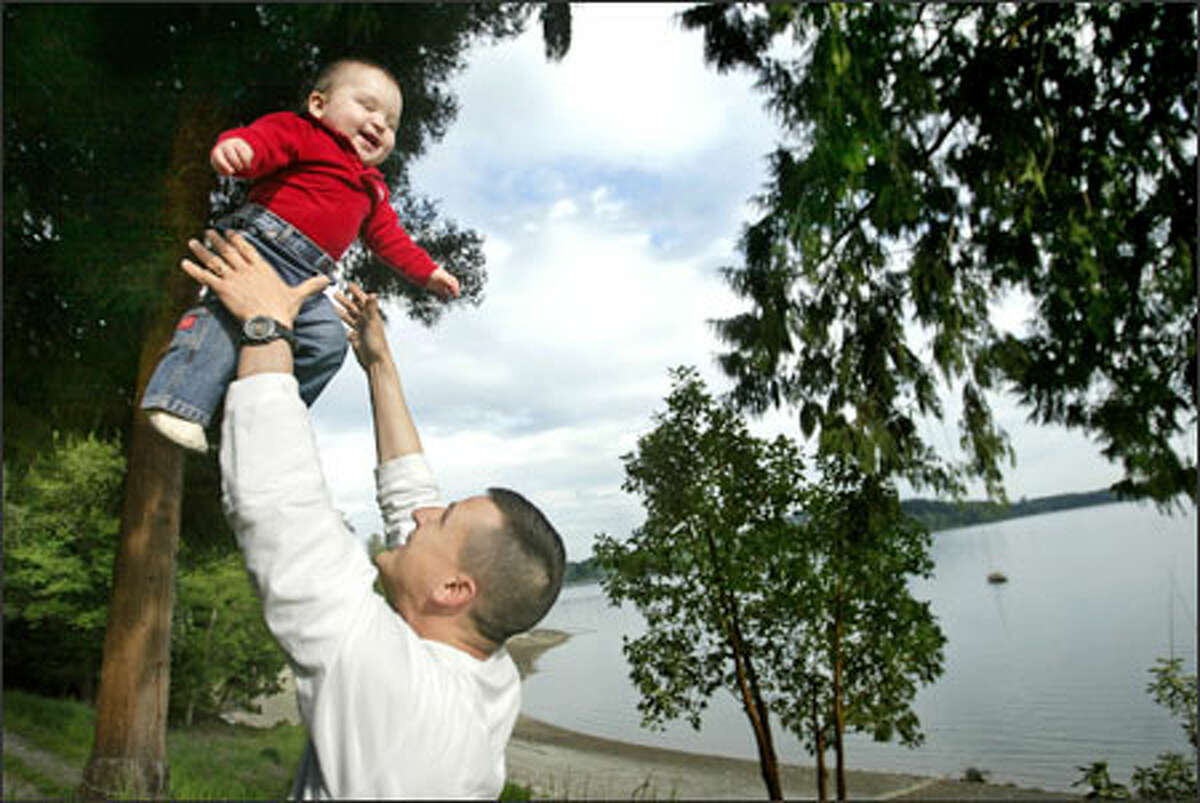 Back from Iraq, Lt. John Adams of the Washington National Guard plays with his son, Ian, on their property in Shelton, where Adams operates a shellfish farm with his father. Adams' deployment, compounded by a medical emergency, put a strain on the family's shellfish business.