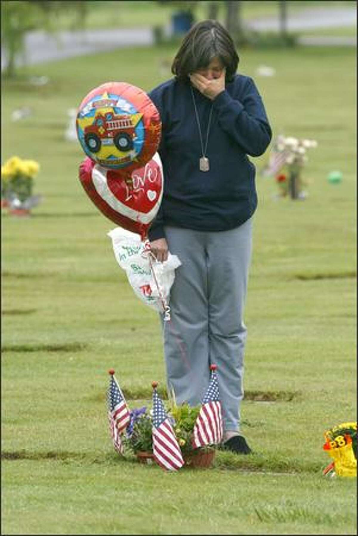 Shellie Starr drops off birthday balloons at the gravesite of her son, Jeff, at the Grand Army of the Republic Cemetery near Snohomish. He was killed last year on Memorial Day, just two days before he would have returned to civilian life.