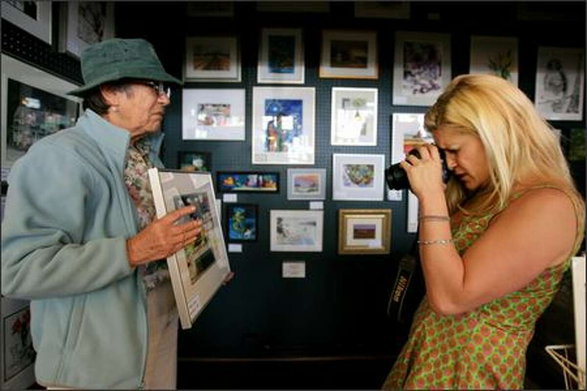 With the help of West Seattle artist Genevieve Ashford, Megan Lee of the Pike Place Market News takes a photograph of a painting at the market's Art Stall Gallery.