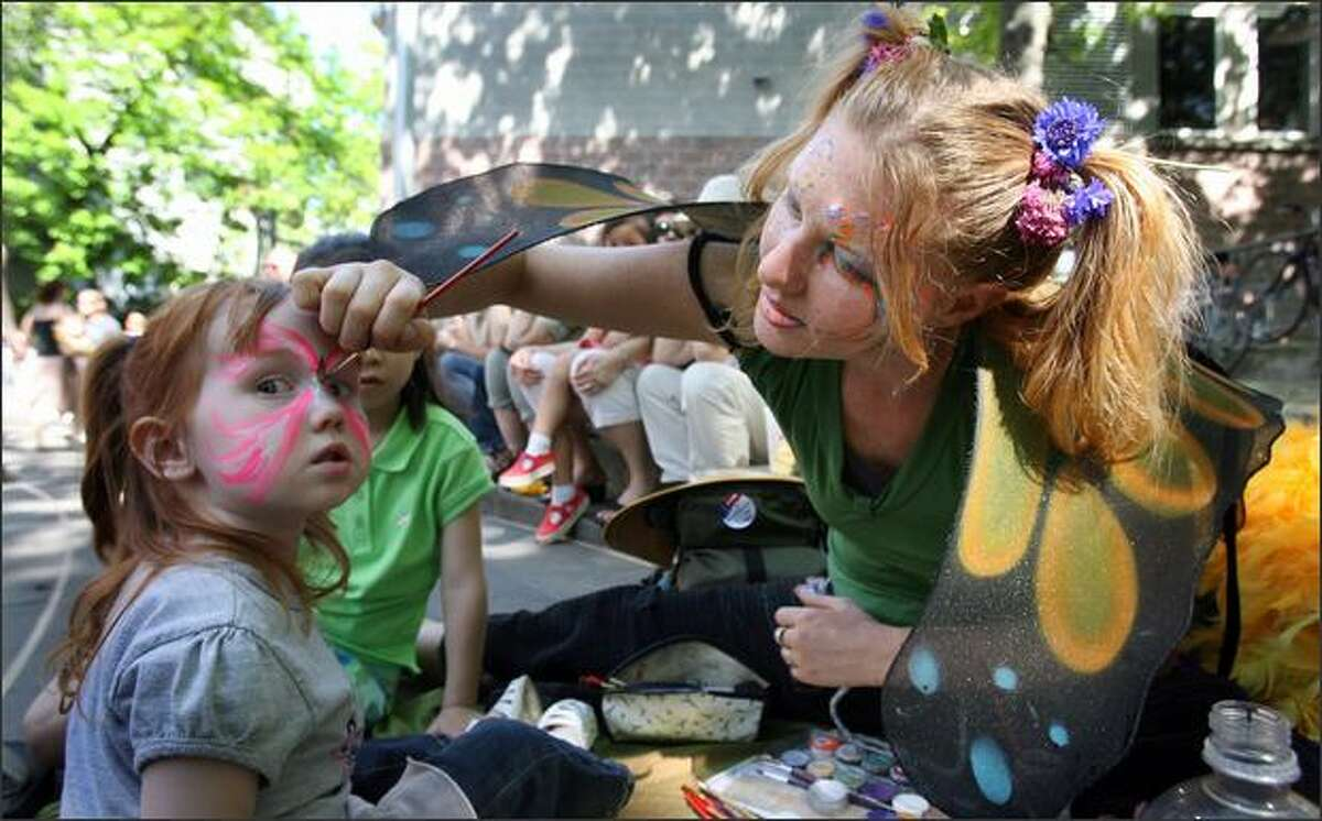 Two-year-old Charis Mooney of Everett has her face painted by Ruth Tru during the Northwest Folklife Festival at the Seattle Center.