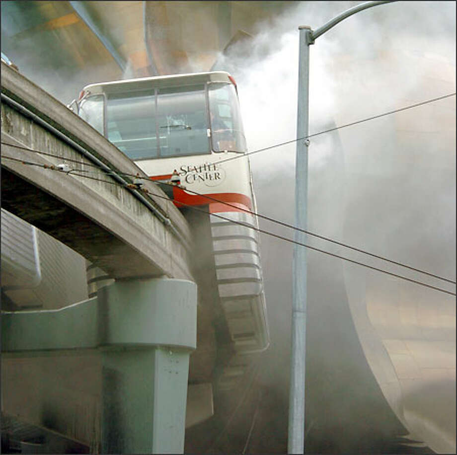 Smoke pours out of one of the Monorail trains after it caught on fire near the Seattle Center.  Eight riders and one firefighter were sent to Harborview Medical Center. Photo: Jeff Larsen, Seattle Post-Intelligencer / Seattle Post-Intelligencer