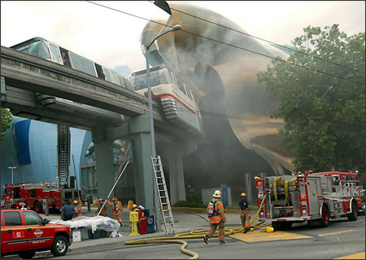 Smoke pours from a burning Monorail car outside the Experience Music Project.
