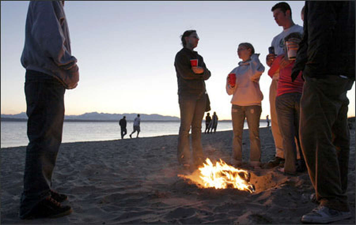 Young visitors to Golden Gardens Beach burn Duraflame logs in an illegal fire pit. People who build bonfires outside the designated fire rings cause a headache for parks officials and often leave a mess for maintenance workers to clean up. Golden Gardens Beach currently has 12 fire rings for bonfires, which are available on a first-come, first-served basis.