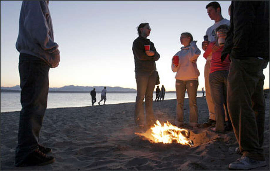 Young visitors to Golden Gardens Beach burn Duraflame logs in an illegal fire pit. People who build bonfires outside the designated fire rings cause a headache for parks officials and often leave a mess for maintenance workers to clean up. Golden Gardens Beach currently has 12 fire rings for bonfires, which are available on a first-come, first-served basis. Photo: Meryl Schenker, Seattle Post-Intelligencer / Seattle Post-Intelligencer