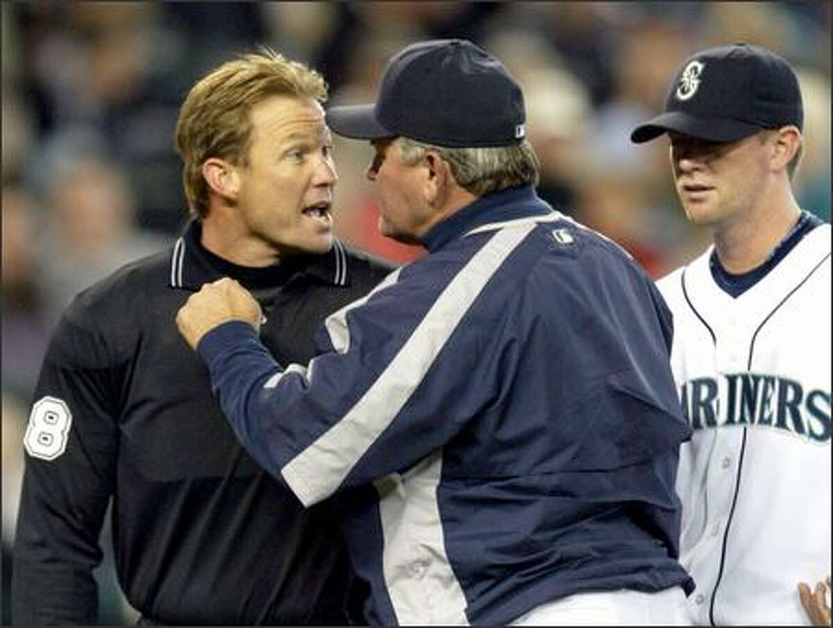 Manager Mike Hargrove gives home plate umpire Jim Wolf an earful as pitcher Ryan Franklin looks on after Wolf tossed Franklin out of Tuesday's game in the third inning for hitting Toronto's Reed Johnson with a pitch. Seattle trailed 7-0 at the time and ended up losing 9-7.