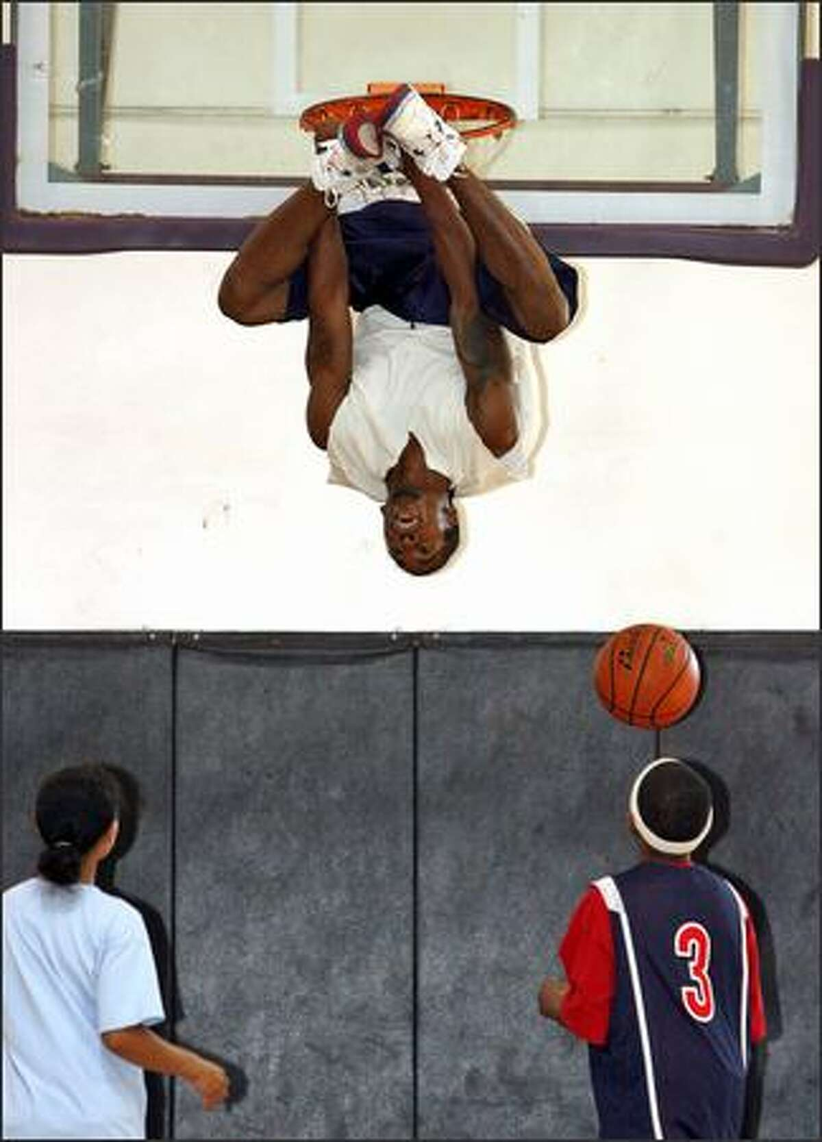 """""""Spyda"""" completes one of his signature inverted dunks for Myah Williams, 11, left, and Arell Hennings, 12, as the Ball4Real Streetball Tour visits the Rotary Boys and Girls Club in Seattle."""