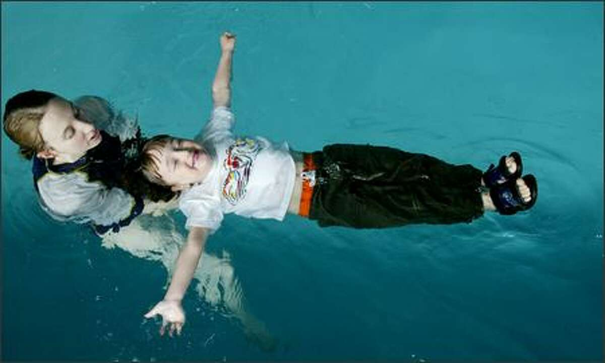 Safe N Sound instructor Courtney Carr teaches Jack Hills, 3, how to conserve his energy by floating. During this water-safety class, students swim fully clothed to simulate falling into the water.