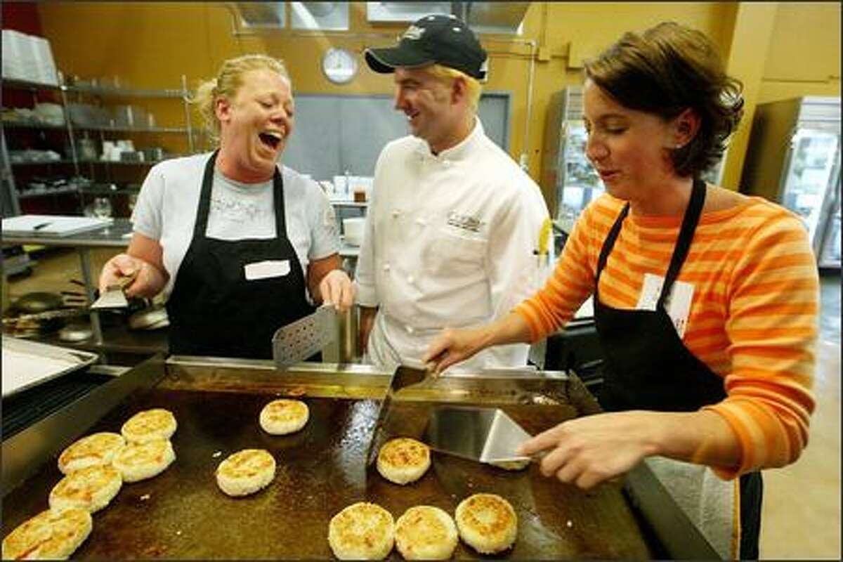 Cuizam! customers Cindy Massey, left, and Krista Golden, both of Duvall, have fun while grilling artichoke risotto cakes under the supervision of chef Rob Mullins.