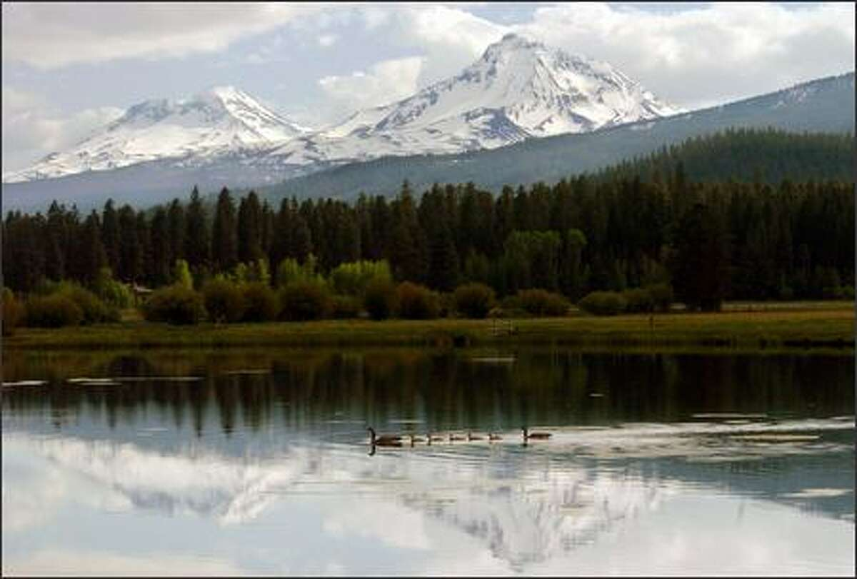 A fishing lake at the Black Butte Resort near Sisters, Ore., reflects two of the Three Sisters peaks, once known as Faith, Hope and Charity.