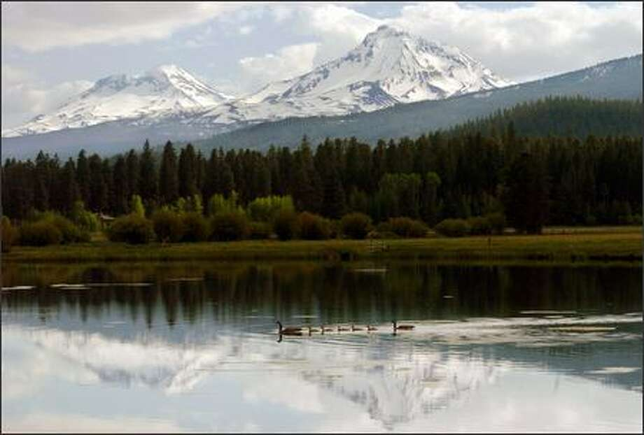 A fishing lake at the Black Butte Resort near Sisters, Ore., reflects two of the Three Sisters peaks, once known as Faith, Hope and Charity. Photo: Jeff Larsen, Seattle Post-Intelligencer / Seattle Post-Intelligencer