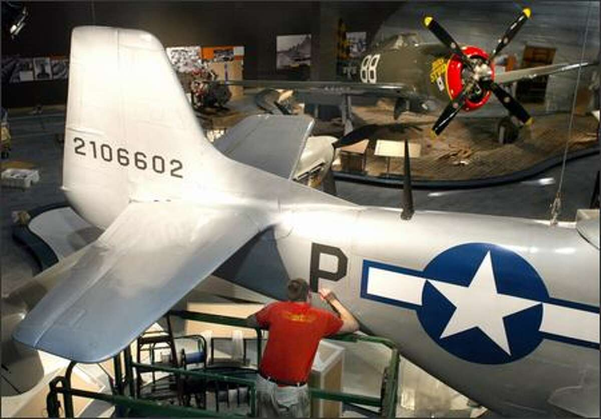 Painter Daniel Lorentz details a World War II-era plane at Boeing's Museum of Flight during preparation for the opening of its Personal Courage Wing.