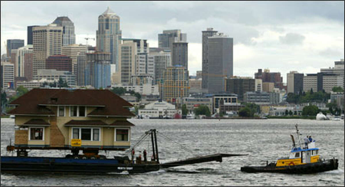 A tugboat pulls a barge carrying the 3,000-square-foot house across Lake Union, bound for the Ballard Locks and, ultimately, Shaw Island in the San Juans.