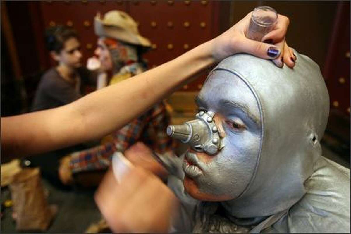 Makeup artist Gina Adams steadies Will Rechoff's head as she applies silver greasepaint to his face. Rechoff, who played the Tin Man in Shorecrest High School's production of