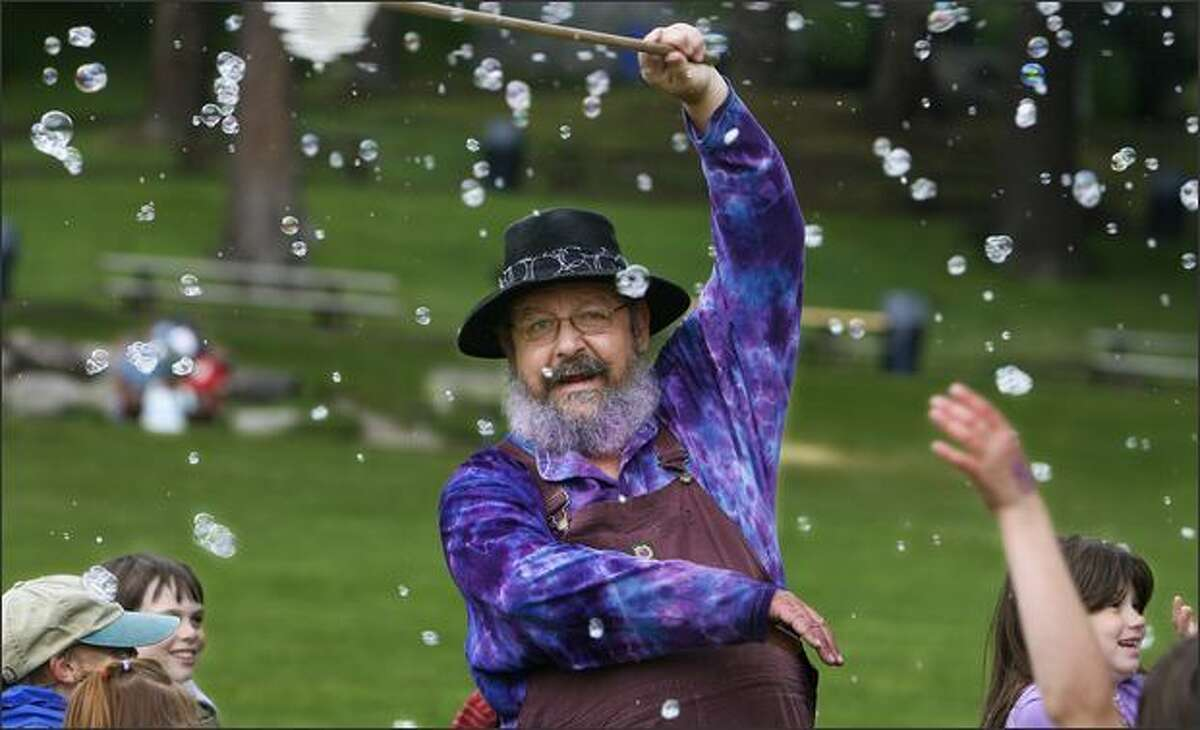 Surrounded by bubbles and a group of energized kids, Gary GoLightly, known as the Bubble Man, entertains kids during an impromptu performance at Carkeek Park.