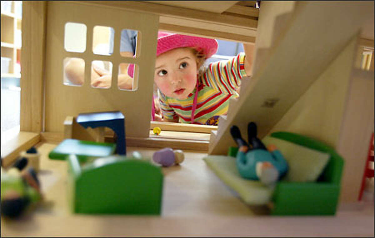 Eleanor Home, 2, of Tacoma checks out a dollhouse in the new play area at Mary Bridge Children's Hospital. Eleanor's newborn sister is at the hospital.