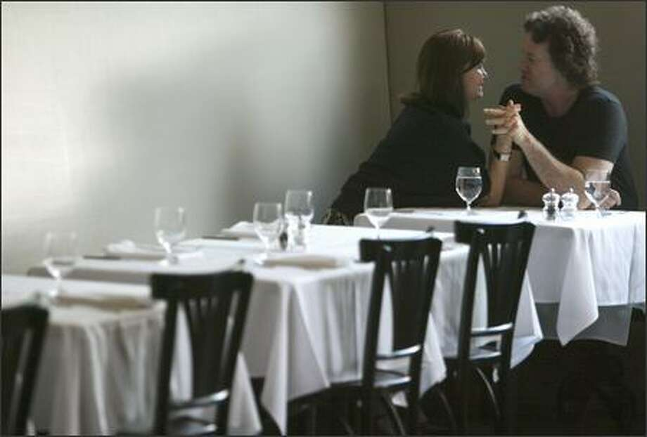 Krista White and Larry Taubman of Orcas Island find an intimate corner at the usually buzzing Crémant in Seattle's Madrona neighborhood. Photo: Mike Urban, Seattle Post-Intelligencer / Seattle Post-Intelligencer