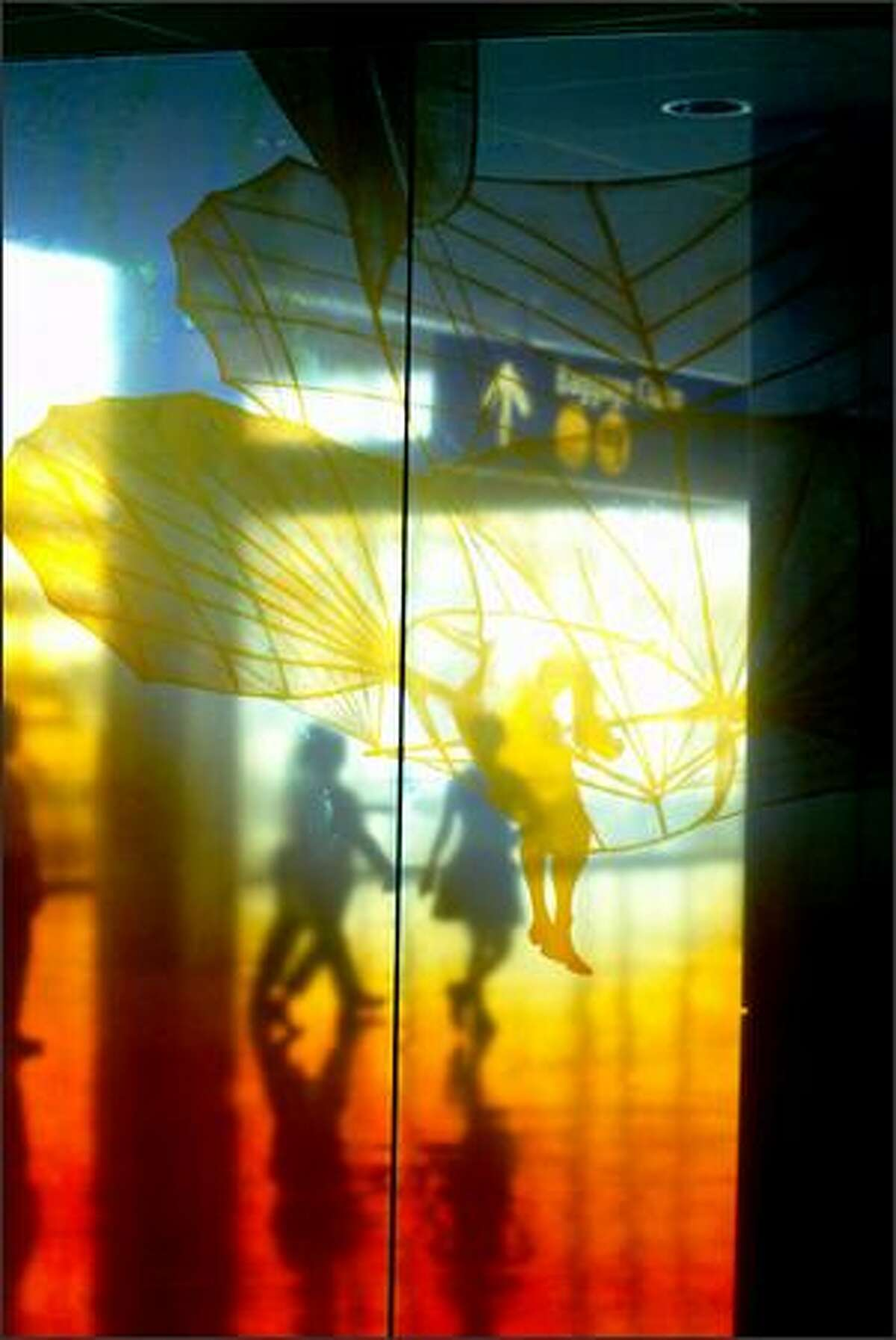 Passengers pass by the new amber glass wall installation that also serves as a security wall in the new Sea-Tac Concourse A. Linda Beaumont's