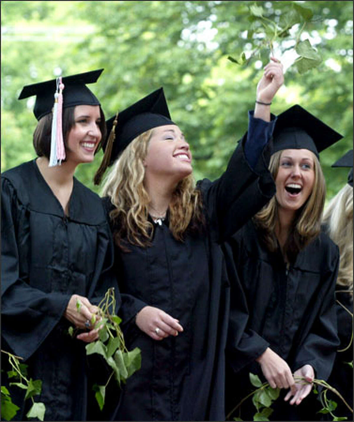 Signifying both the student's tie to Seattle Pacific University and the independence that comes with graduation, Jessika Flood holds a sprig of ivy in the air after a traditional ivy-cutting ceremony on campus. She celebrated the occasion with friends Carly Ferguson, left, and Megan McDowell, right.