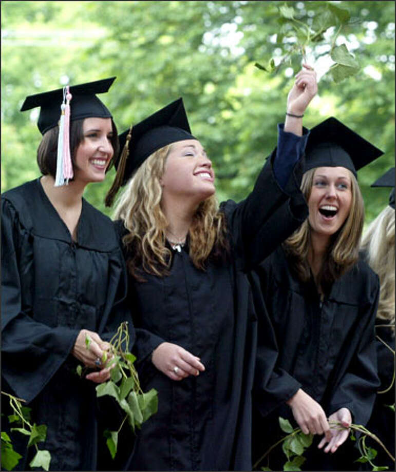 Signifying both the student's tie to Seattle Pacific University and the independence that comes with graduation, Jessika Flood holds a sprig of ivy in the air after a traditional ivy-cutting ceremony on campus. She  celebrated the occasion with friends Carly Ferguson, left, and Megan McDowell, right. Photo: Meryl Schenker, Seattle Post-Intelligencer / Seattle Post-Intelligencer
