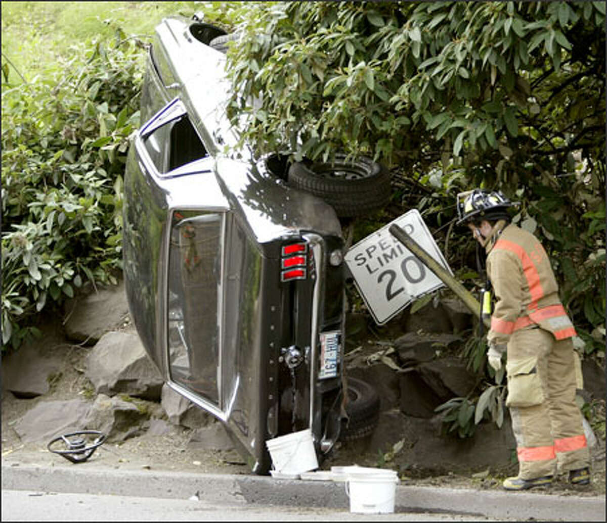 A Seattle firefighter surveys the scene of an accident near the University of Washington. A driver, who declined to give his name, lost control of his car and crashed into a rock retaining wall when his steering wheel came off on Pend Oreille Road at the northeast entrance to the campus.