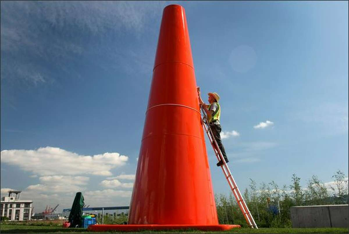 """Richard Shanks takes advantage of Thursday's blue skies and applies polish to Dennis Oppenheim's """"Safety Cones,"""" a temporary exhibit at the Olympic Sculpture Park. """"Safety Cones"""" will be on display through October. The artist is described as someone who """"playfully manipulates scale and everyday objects."""""""
