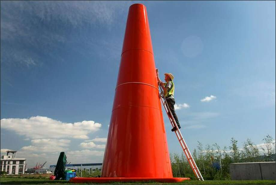 "Richard Shanks takes advantage of Thursday's blue skies and applies polish to Dennis Oppenheim's ""Safety Cones,"" a temporary exhibit at the Olympic Sculpture Park. ""Safety Cones"" will be on display through October. The artist is described as someone who ""playfully manipulates scale and everyday objects."" Photo: Joshua Trujillo, Seattlepi.com / seattlepi.com"