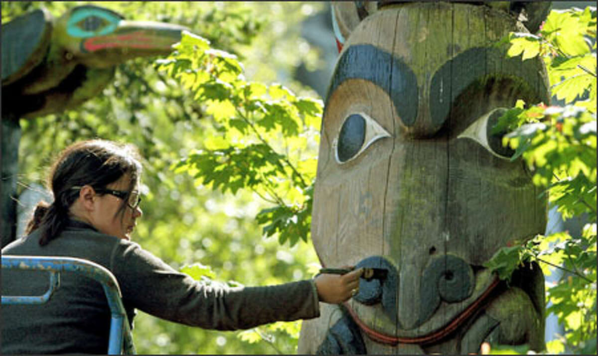 Jessie Groeschen, a Seattle woodcarving artist, adds black paint to one of the totem poles on display at Ivar's Salmon House in Seattle. Groeschen will refurbish more than 25 totem poles and 10 shields by sanding and painting them. The 18-foot cedar totem pole, carved in 1967 by Bill Neidinger and Jim Johnson, was purchased by Ivar Haglund in 1969 for the north Lake Union restaurant's opening.