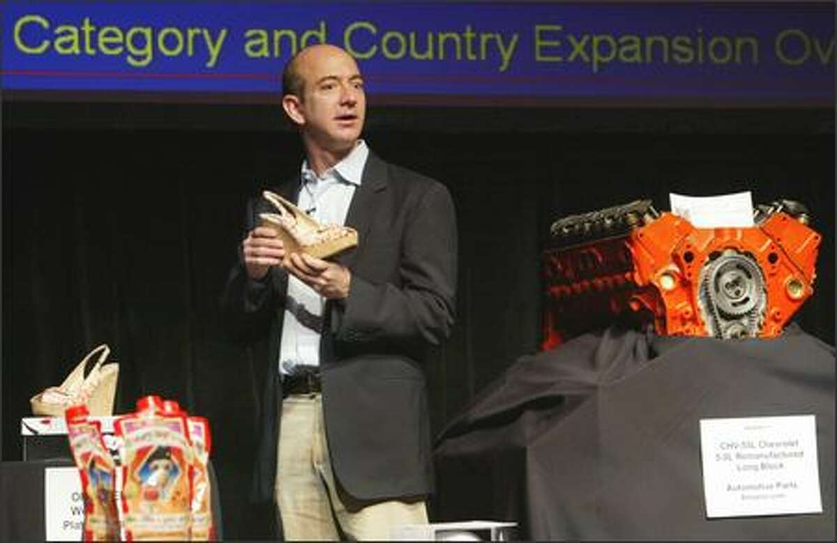 """At the annual shareholders meeting Thursday in Seattle, Amazon.com Chief Executive Jeff Bezos displays some products offered on the Web site, including shoes, ready-mix daiquiris and a remanufactured Chevy 5.0-liter long-block engine. Of the shoes, Bezos joked, """"When I wear them, they make my calves look pretty good."""""""