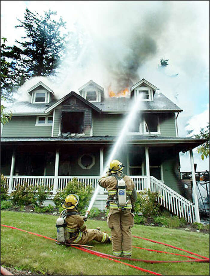 Firefighters pour water onto the flaming roof of a house near Kirkland yesterday. The fire, which witnesses said started in the garage, destroyed the house, whose owner designed the wooden structure. Photo: Grant M. Haller, Seattle Post-Intelligencer / Seattle Post-Intelligencer