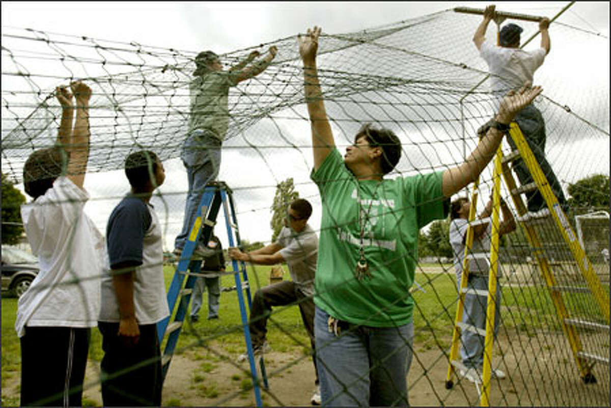 Carmen Martinez, center right, the teen development leader with Seattle Parks and Recreation, helps parent and neighborhood volunteers erect a batting cage yesterday at the South Park Community Center.
